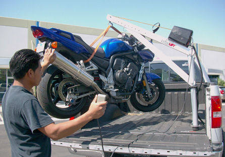 portable hoist lifting motorcycle into pickup truck